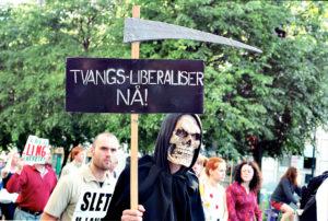 """""""Tvangsliberaliser eller dø"""" - plakat fra demonstrasjon mot handelsurettferdighet"""