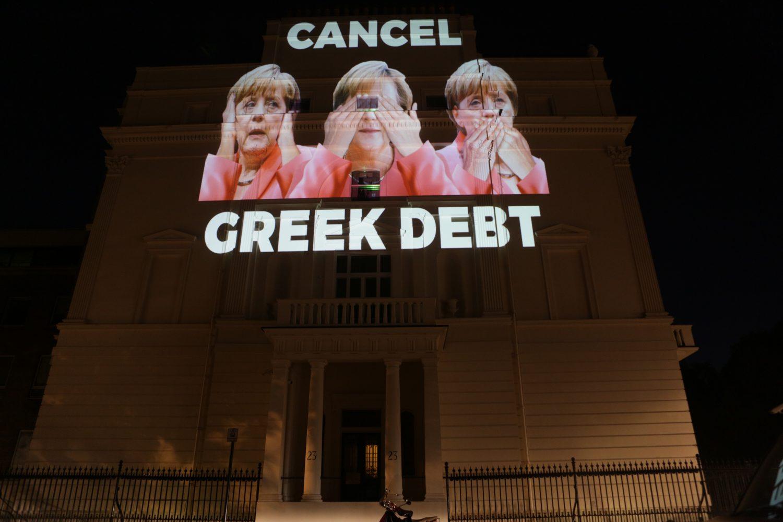 Cancel Greek Debt (projeksjon av Merkel som holder seg for ørene, for øynene og for munnen, på den tyske ambassaden i London)
