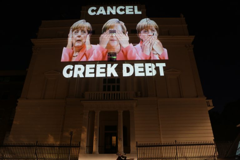 Cancel Greek Debt (projeksjon av Merkel som holder seg for ørene, for øynene og for munnen, på den tyske ambassaden i London)