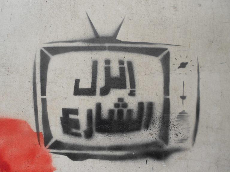 """Grafitti av en TV med arabisk tekst: """"Gå i gatene"""""""