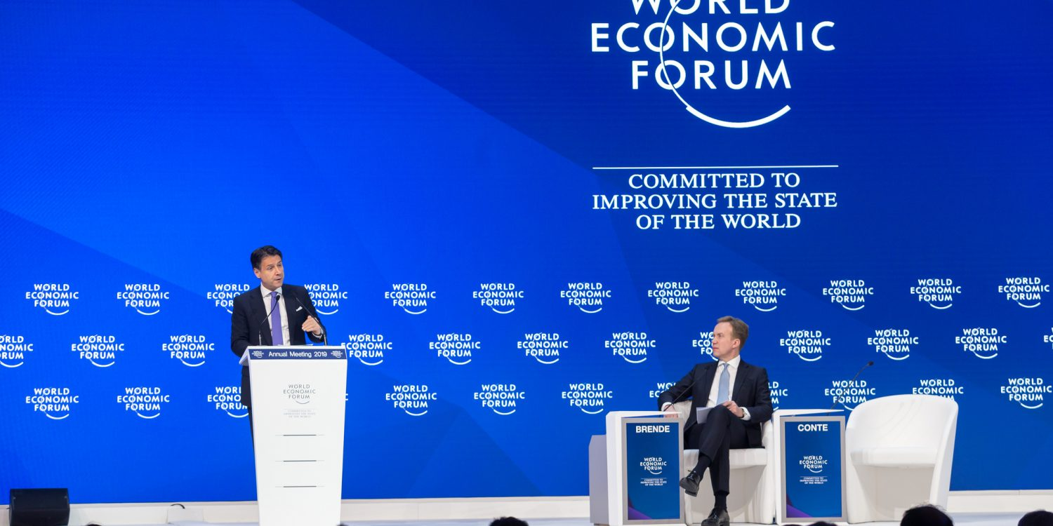 """World Economic Forum - Commited to improving the state of the World"" står i bakgrunnen mens Børge Brende sitter og Giuseppe Conte snakker."