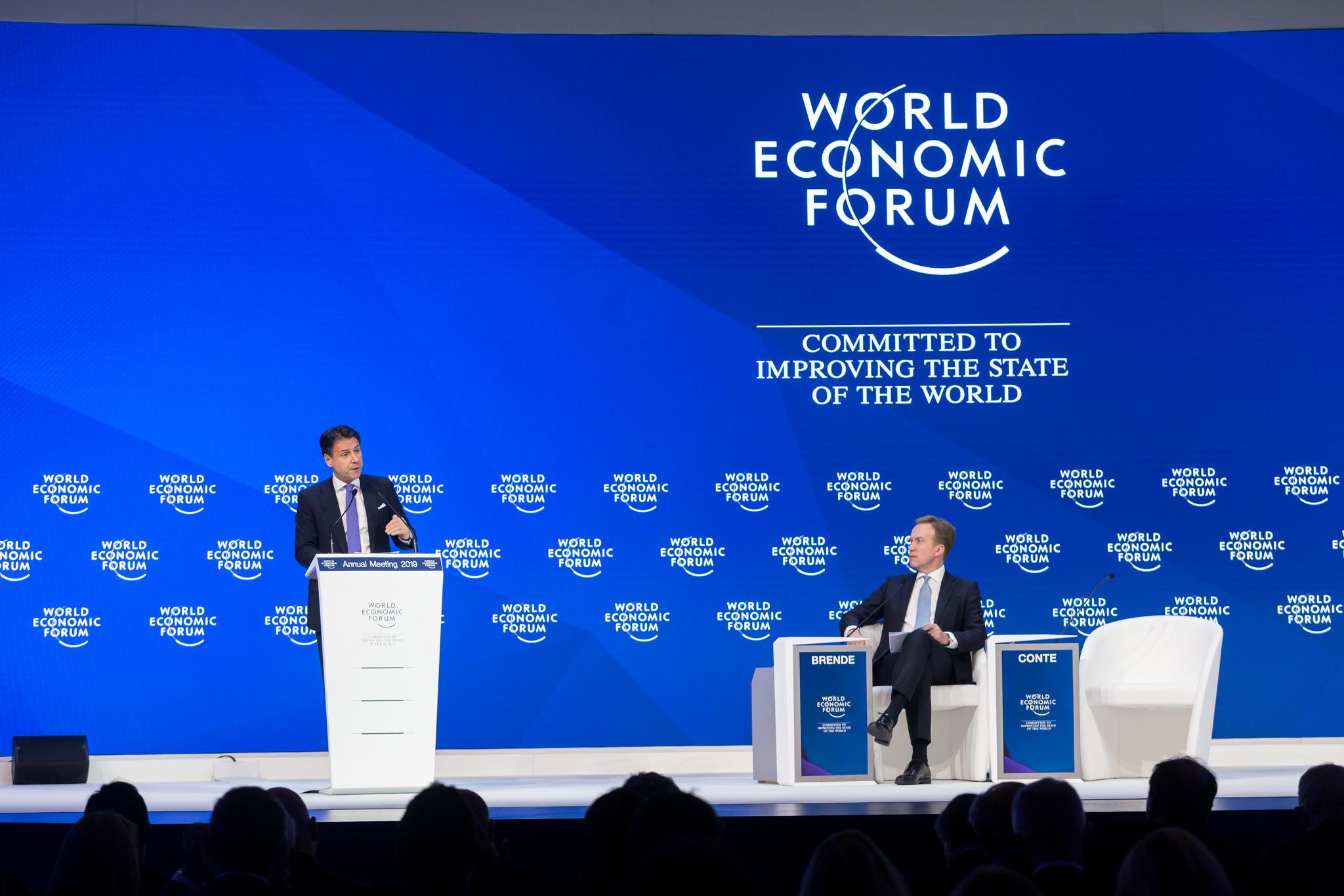 """""""World Economic Forum - Commited to improving the state of the World"""" står i bakgrunnen mens Børge Brende sitter og Giuseppe Conte snakker."""