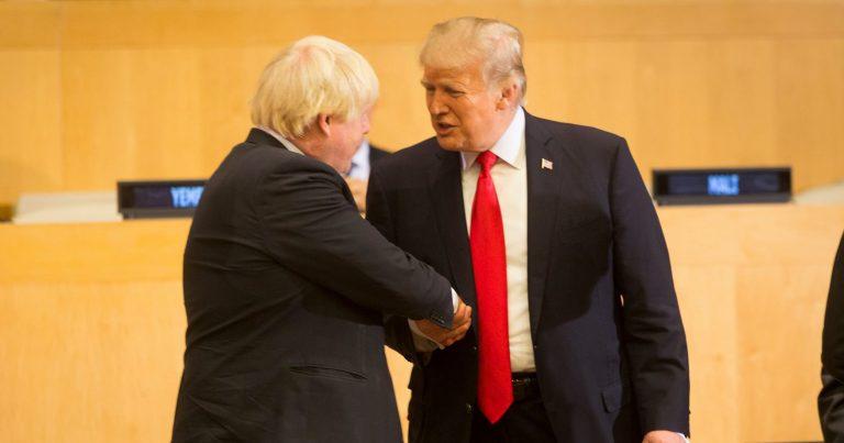 Donald Trump og Boris Johnshon tar hverandre i hånda.