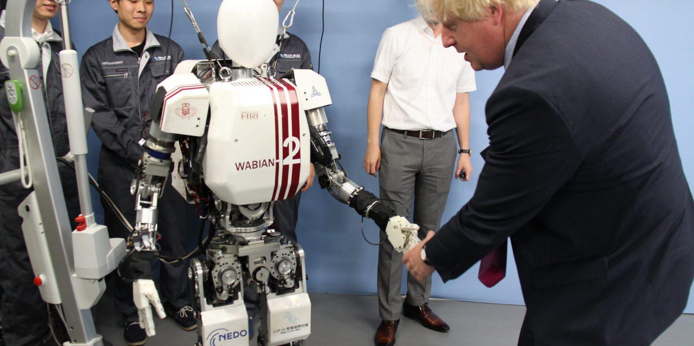 Bois Johnson tar en robot i hånden.